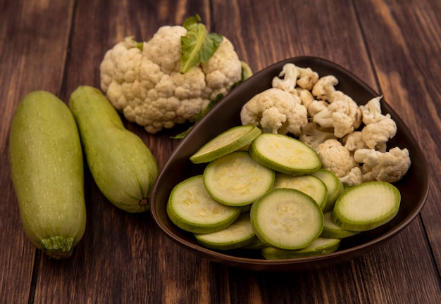 Top view of fresh chopped zucchinis and cauliflower buds on a bowl with whole zucchinis and cauliflower isolated on a wooden wall