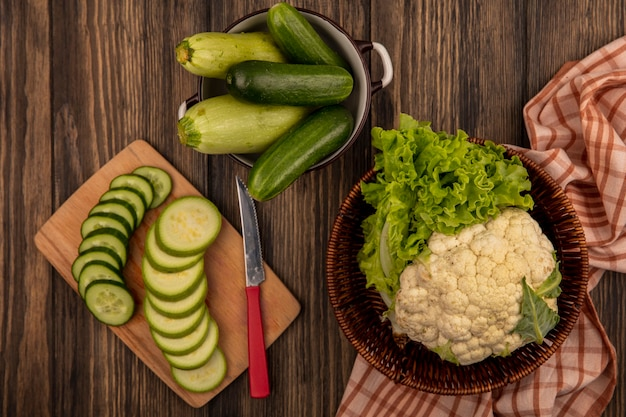 Top view of fresh chopped zucchinis on a wooden kitchen board with cucumbers on a bowl with cauliflower and lettuce on a bucket on a checked cloth on a wooden background