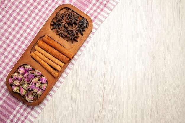 Vista dall'alto cannella fresca con fiori sul colore della pianta del fiore della scrivania bianca