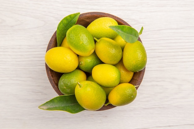 白い背景の上のプレート内の新鮮な柑橘系の果物の上面図フルーツトロピカル熟したダイエットエキゾチックな色