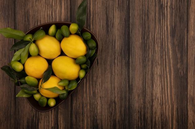 Vista dall'alto di agrumi freschi come limoni e kinkan su una ciotola su una superficie in legno con spazio di copia