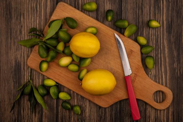 Vista dall'alto di agrumi freschi come limoni e kinkan su una tavola da cucina in legno con coltello su una superficie di legno