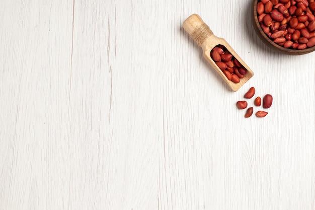 Vista dall'alto arachidi fresche e pulite all'interno del piatto su una scrivania bianca leggera dadi molti snack a conchiglia di piante di alberi