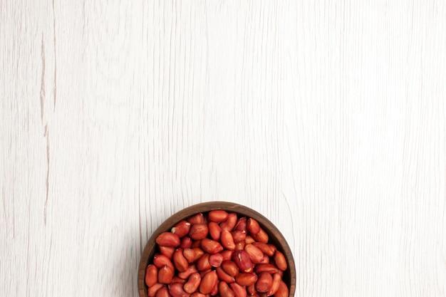 Vista dall'alto di arachidi fresche e pulite all'interno del piatto su dadi da scrivania bianchi molti snack di conchiglie di piante di alberi