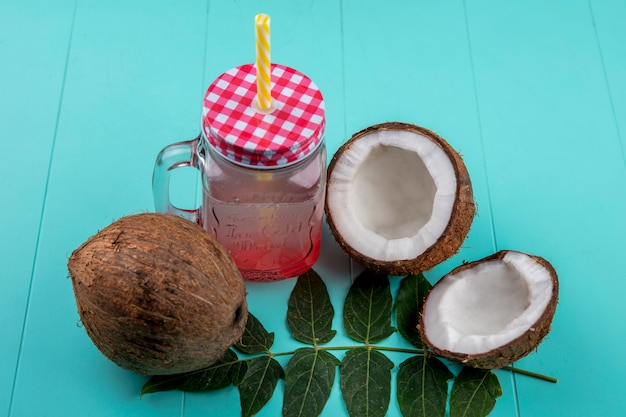 Top view of fresh coconut with leaves and juice in glass jar on blue