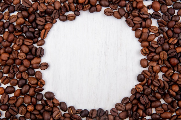 Top view of fresh coffee beans isolated on a white background with copy space