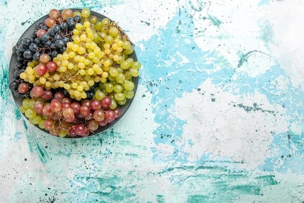 Vista dall'alto uva fresca colorata frutta succosa e pastosa su scrivania azzurra frutta bacca fresca succhi di frutta vino