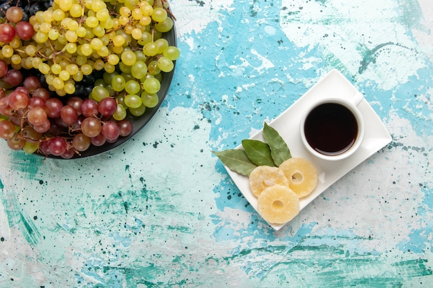 Vista dall'alto uva fresca colorata frutta succosa e pastosa con una tazza di tè su sfondo azzurro frutti berry fresco succo dolce vino