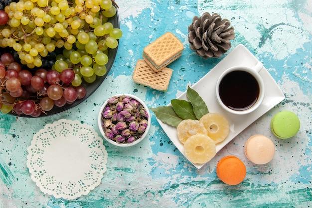 Vista dall'alto fresche uve colorate con tazza di tè macarons e cialde su sfondo blu frutti di bosco fresco mellow succo di vino