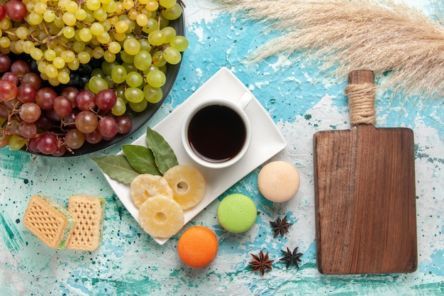 Top view fresh colored grapes with cup of tea macarons and waffles on the blue background fruits cookie sugar sweet cake bake pie
