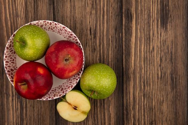 Vista dall'alto di mele fresche e colorate su una ciotola con mele verdi isolate su una parete in legno con spazio di copia