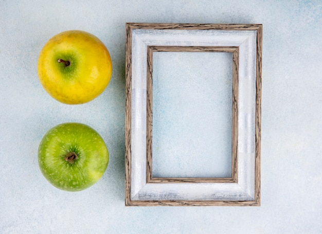 Top view of fresh and colorful apples with empty photo frame with on white