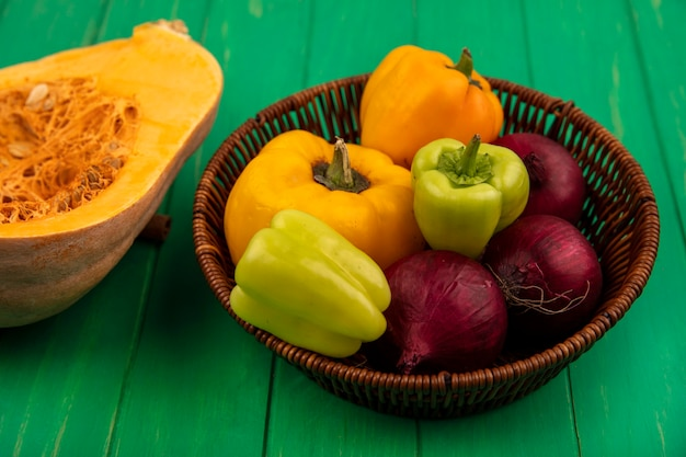 Top view of fresh colorful bell peppers on a bucket with red onion with pumpkin isolated on a green wooden wall