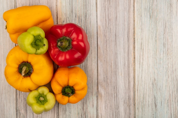 Top view of fresh colorful bell peppers isolated on a grey wooden surface with copy space