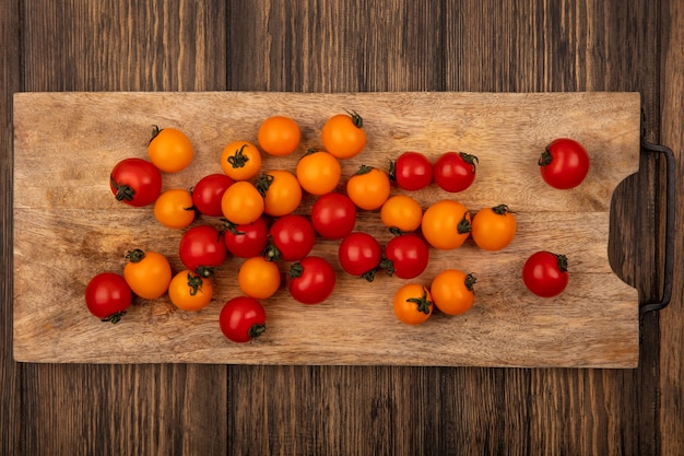Top view of fresh colorful cherry tomatoes isolated on a wooden kitchen board on a wooden wall