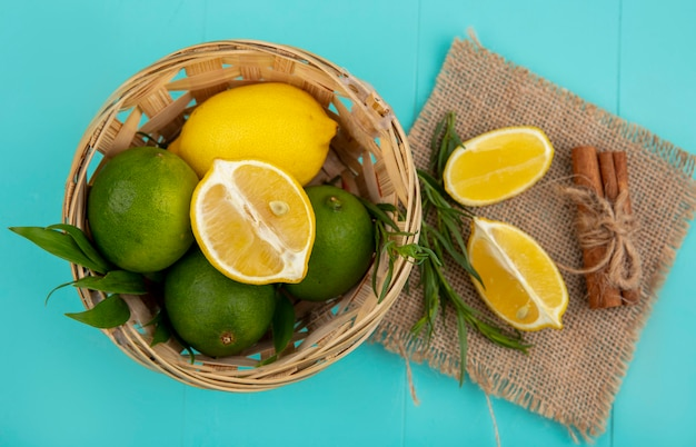 Top view of fresh and colorful lemons on bucket with slices of lemonnd green tarragon on sack cloth on blue