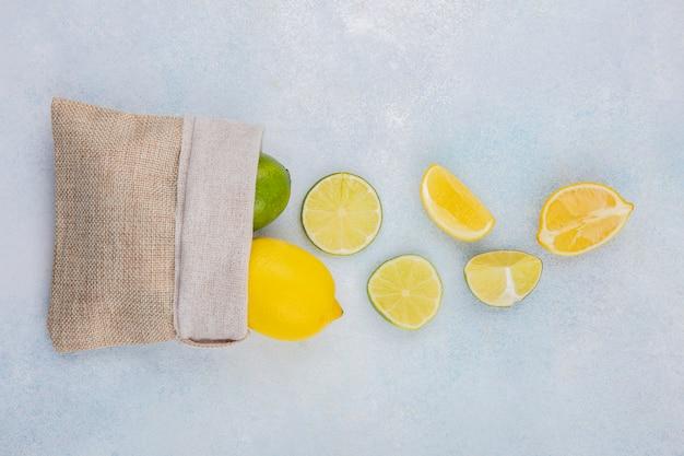 Vista dall'alto di limoni freschi e colorati sul sacchetto di tela da imballaggio isolato su bianco
