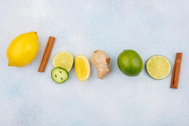 Vista dall'alto di limoni freschi e colorati con bastoncini di cannella allo zenzero con fette di cetriolo su bianco