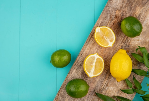 Vista dall'alto di limoni freschi e colorati sul bordo della cucina in legno sul blu