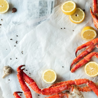 Top view of fresh crab phalanges with lemon and spices on rumpled paper.