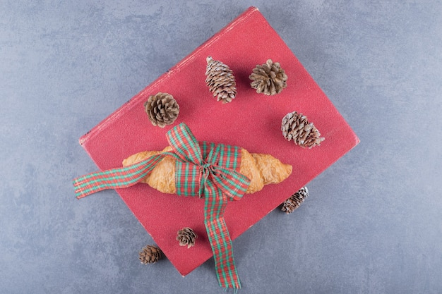 Top view of fresh croissant and decorative pine cones over red book.
