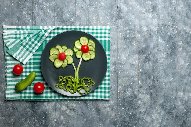 Vista dall'alto di cetrioli freschi fiore progettato insalata su pavimento grigio insalata di verdure pasto salutare