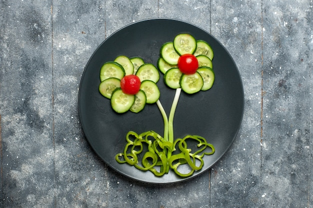 Top view fresh cucumbers flower designed salad on grey space