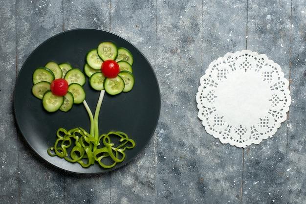 灰色のスペースに新鮮なキュウリの花がデザインしたサラダの上面図