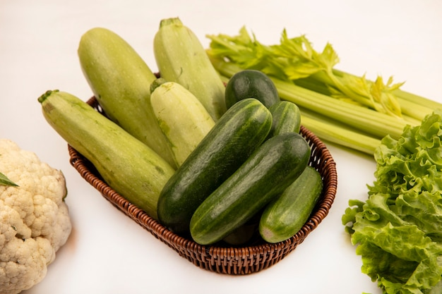 Top view of fresh cucumbers and zucchinis on a bucket with cauliflower celery and lettuce isolated on a white wall