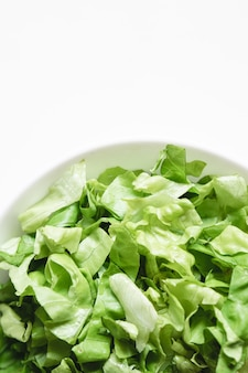 Top view of fresh cut lettuce on a plate on a white.