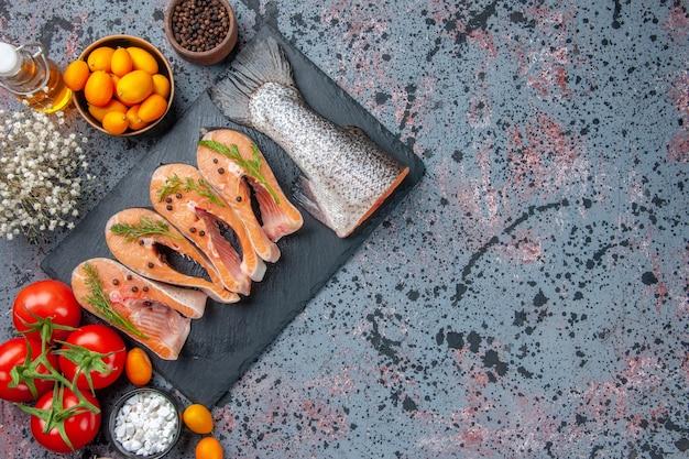 Vista dall'alto di pesce crudo tagliato fresco verde sul vassoio di colore scuro spezie kumquat bottiglia di olio sulla tabella dei colori della miscela nera blu