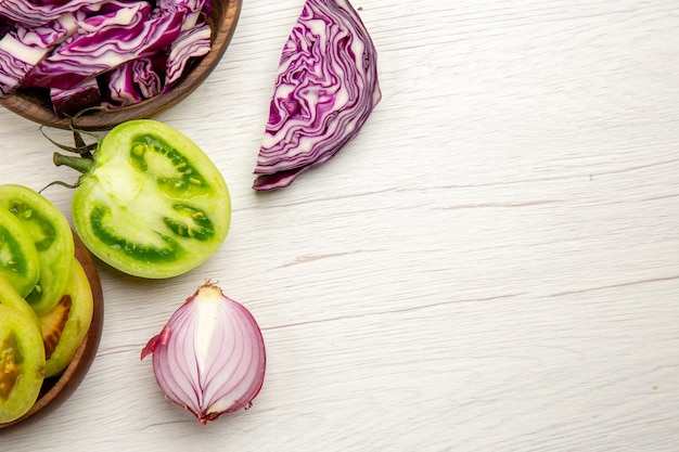 Top view fresh cut vegetables green tomatoes red cabbage in bowls red onion on white wooden surface with free space