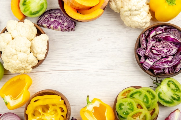 Top view fresh cut vegetables green tomatoes red cabbage onion pumpkin cauliflower yellow bell pepper in bowls on white wooden surface free space in center