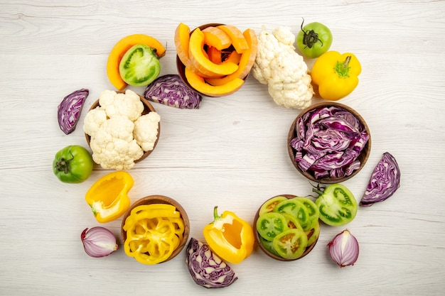 Top view fresh cut vegetables green tomatoes red cabbage onion pumpkin cauliflower yellow bell pepper in bowls on white wooden surface with free space