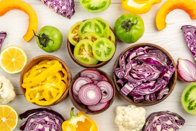 Vista dall'alto verdure fresche tagliate cavolo rosso pomodoro verde zucca cipolla rossa peperone giallo cavolfiore limone in piccole ciotole su superficie bianca