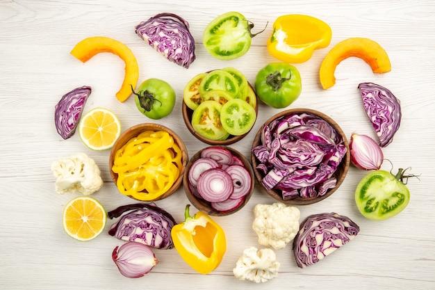Vista dall'alto verdure fresche tagliate cavolo rosso pomodoro verde zucca cipolla rossa peperone giallo cavolfiore limone in piccole ciotole su superficie di legno bianca