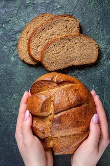 暗い机の上に女性の手で上面図焼きたての暗いパン