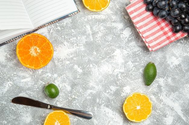 Vista dall'alto uva scura fresca con arance su superficie bianca frutta matura albero dolce vitamina fresca