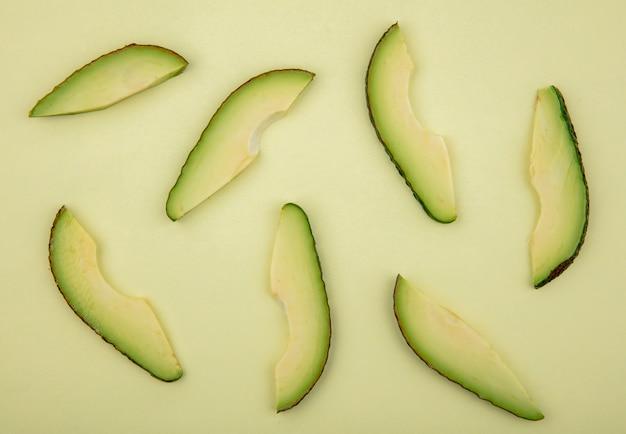 Vista dall'alto di fette di avocado fresche e deliziose isolate su verde chiaro
