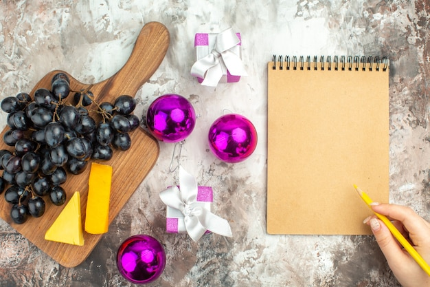 Top view of fresh delicious black grape bunch and cheese on wooden cutting board and gifts decoration accessories and hand writing on notebook on mixed color background