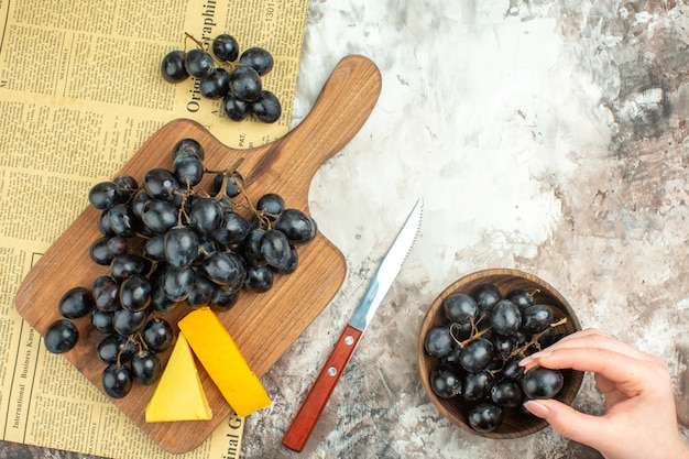 Top view of fresh delicious black grape bunch and various kinds of cheese on wooden cutting board and in a brown pot knife on mixed color background