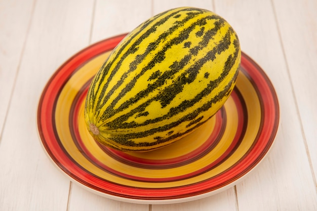 Top view of fresh and delicious cantaloupe melon on a plate on a white wooden surface