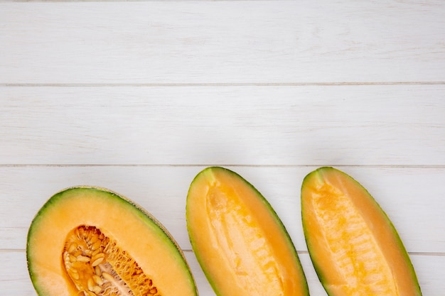 Top view of fresh and delicious cantaloupe melon slices on white wood with copy space