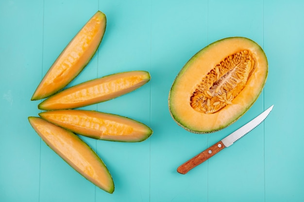 Top view of fresh and delicious cantaloupe melon slices with a knife on blue