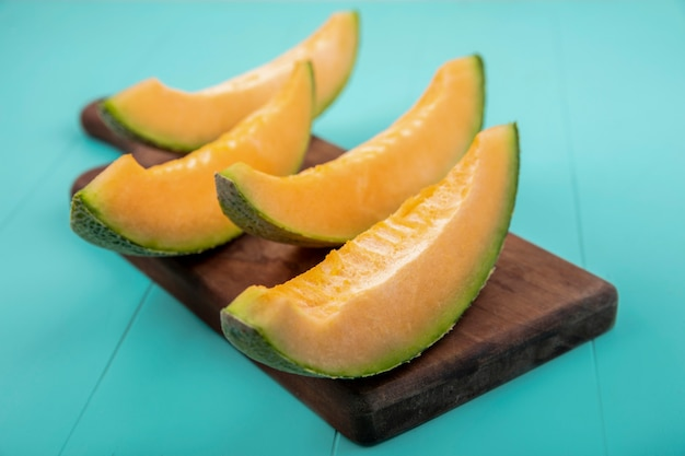 Top view of fresh and delicious cantaloupe melon slices on wooden kitchen board on blue