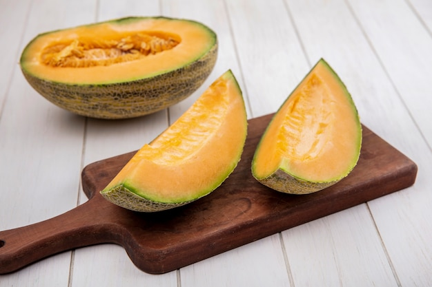 Top view fresh and delicious cantaloupe melon slices on wooden kitchen board on white wood