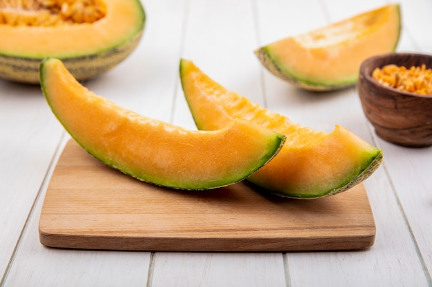 Top view of fresh and delicious cantaloupe melon slices on wooden kitchen board on white wood