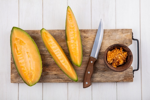Top view of fresh and delicious cantaloupe melon slices on wooden kitchen board with knife on white wood