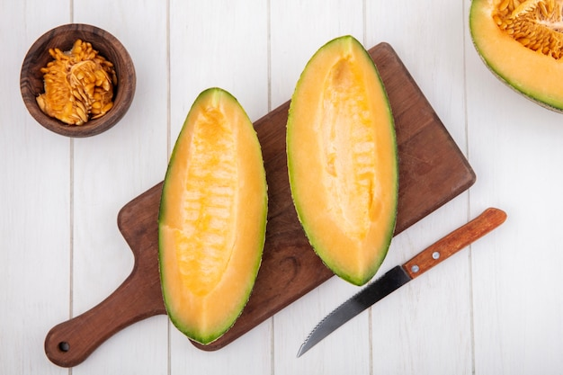Top view of fresh and delicious cantaloupe melon slices on wooden kitchen board with knife with seeds on wooden bowl on white wood