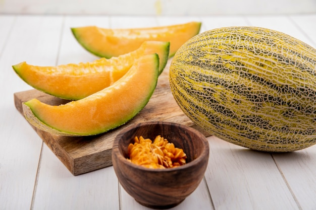 Top view of fresh and delicious cantaloupe melon slices on wooden kitchen board with seeds of melon on wooden bowl on white wood